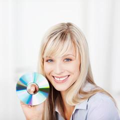 lachende frau zeigt cd