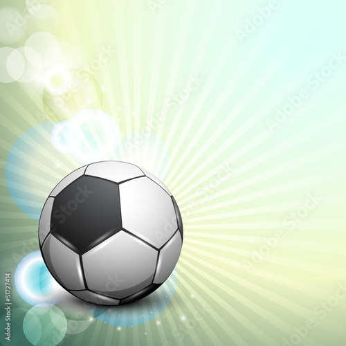 Shiny soccer ball on rays background and space for your message.