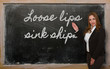 Teacher showing Loose lips sink ships on blackboard