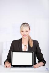 lächelnde beraterin zeigt etwas am laptop