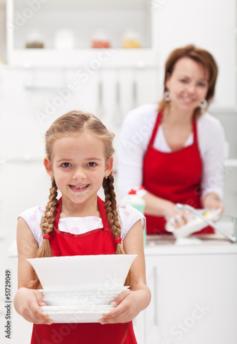 Little girtl helping mother to do the dishes