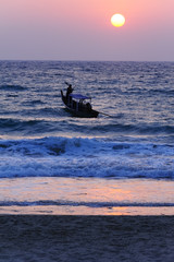 Fishing boat going out towards the setting sun.