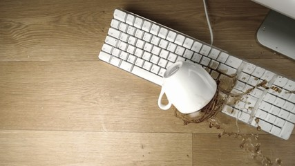 Cup of tea spilled out over a white keyboard