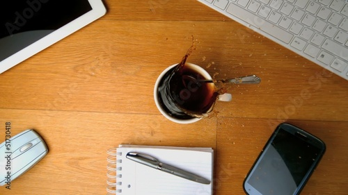 Spoon falling into  coffee and splashing a desk with tablet pc