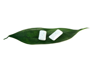 Two chewing gum pieces on green leaf. Isolated.