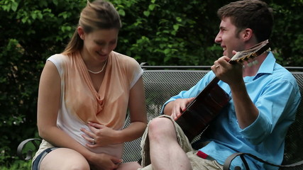 A husband plays guitar and sings to his pregnant wife.