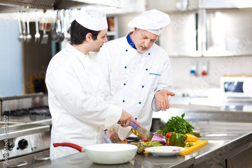 Two chefs cooking in a restaurant kitchen