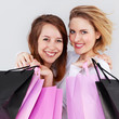 Two pretty girls with shopping bags are so happy