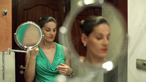 Woman doing makeup in front of mirror and talking on cellphone