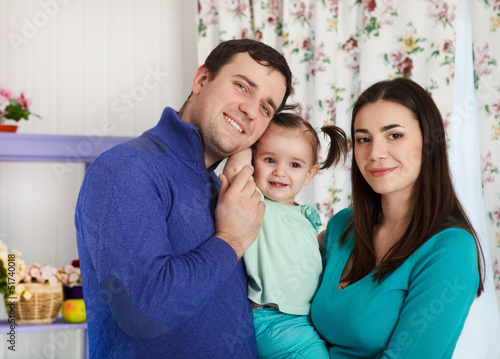 Happy smiling family with one year old baby girl