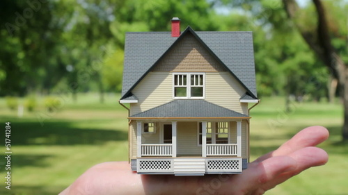 Hand lifting model house into empty lot