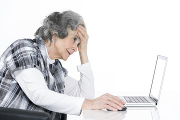 Ältere Frau mit grauen Haaren sitz am Laptop und ist überfordert