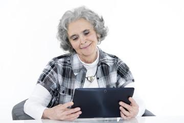 Oma sitzt am Tisch mit iPad in der Hand & guckt aufs Tablet