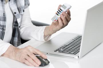 Oma beim online Banking mit Chiptan Generator in der Hand