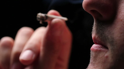 Man smoking a joint, close up on black