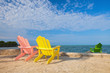 Summer scene with colorful lounge chairs on a tropical beach