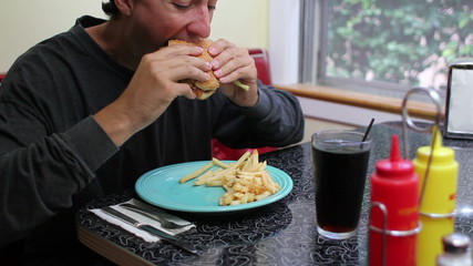 Unhealthy Eating, man eating fast food hamburger