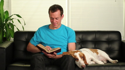 Man is reading, stops and pets his dog