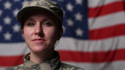 Female soldier in front of US flag, looking up