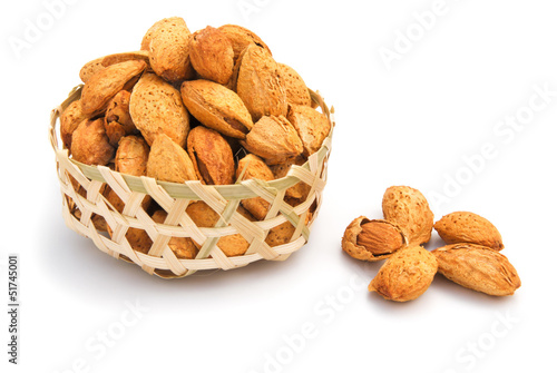 almond nuts in weaven basket on white