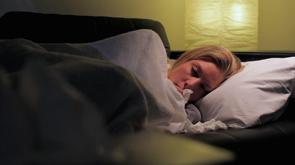 Woman home sick on the couch, dolly shot