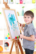 Little boy painting paints picture on easel