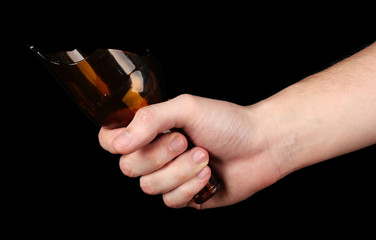 Male hand with broken glass bottle, isolated on black