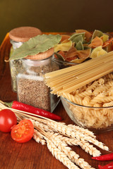 Different types of pasta, spices, tomatoes on a wooden table