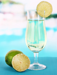 Green cocktail with lime on table on bright background
