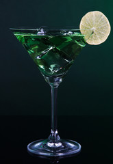 Green cocktail with lime on dark green background