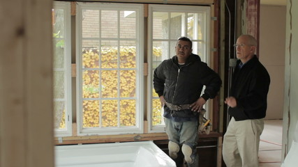 Architect and contractor looking at renovation plans