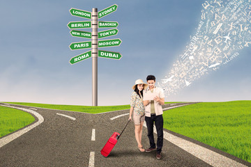 Couple travel at cross road using e-tablet