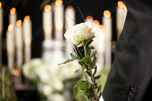 Grief - man with white roses at urn funeral