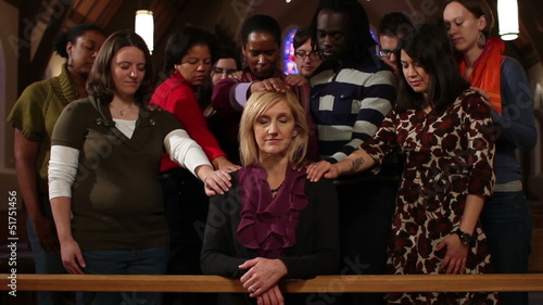Woman praying with community laying hands on her, dolly shot