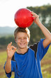 Boy doing okay sign with soccer ball.