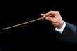 Conductors hand with baton.