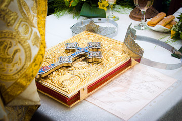 Wedding crowns and cross on a bible prepared for ceremony