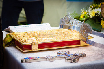 Wedding crowns, cross and bible prepared for ceremony