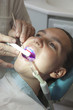 Dentist finishing dental examination with ultraviolet light
