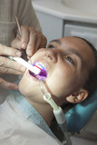 Dentist finishing dental examination with ultraviolet light poster