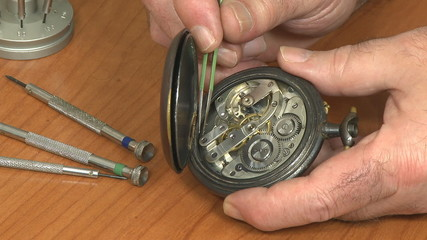 Watchmaker examines pocket watch