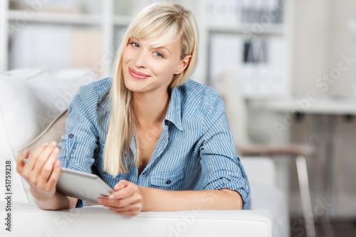 frau liegt mit tablet auf dem sofa