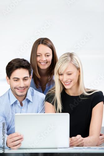 kollegen schauen zusammen auf laptop