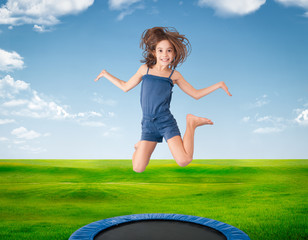 cheerful girl jumping on a meadow