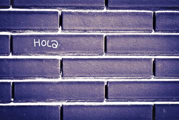 Palabra hola en español escrita en una pared de ladrillos