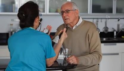 Caucasian nurse checking blood pressure of senior man