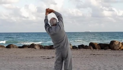 Senior Caucasian man stretching at the beach
