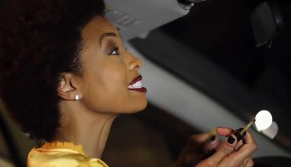 African American woman putting on make up