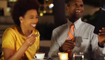 African American couple ordering from menu in cafe