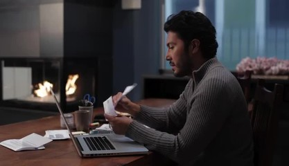 Hispanic man at home with laptop sorting bills